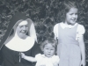 1945: With her sister Peggy and new little sister, Bernie, who have come for a visit from Victoria, B.C., Canada. This is Kate's second of three years of temporary profession, a period during which she commits to the vows of poverty, chastity, and obedience for three years. With temporary profession, she begins wearing the complete and formal habit of her religious order. (From Photo Gallery II. The First Twenty-Five Years as a Sister)